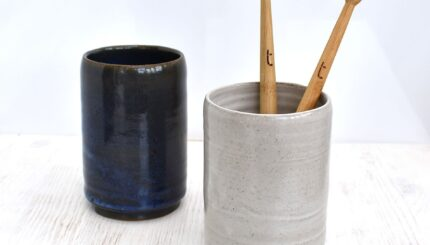 Two bamboo toothbrushes in a grey Clod & Pebble ceramic toothbrush holder