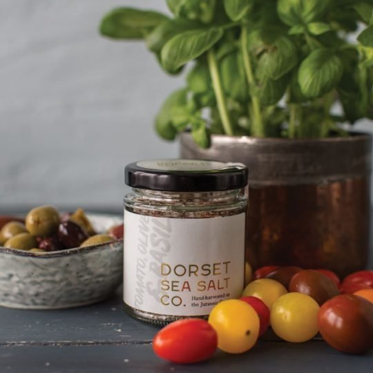 Dorset Sea Salt Flakes Tomato, Olive & Basil Infused pictured next to loose tomatoes and olives